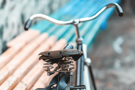 An old bicycle seat with a spring shock absorber. Vintage bicycle on the stone wall background.
