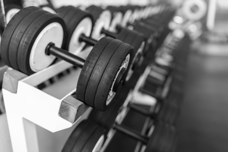 Rows of dumbbells in the gym with hign contrast light Imagens