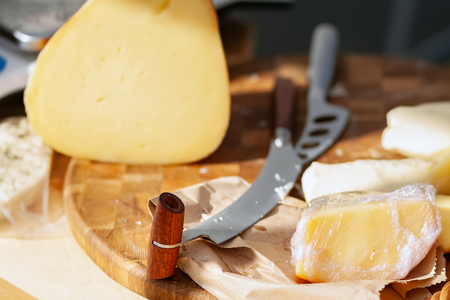Knife for slicing cheese. Production of natural cheese.