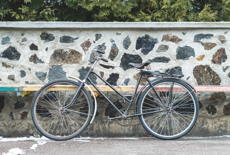 Vintage bicycle on the stone wall background. Afternoon in small european town
