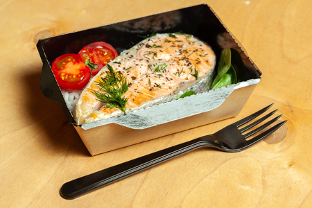 Grilled trout with rice and cherry tomatoes in black lunchbox on wooden backround Stock Photo