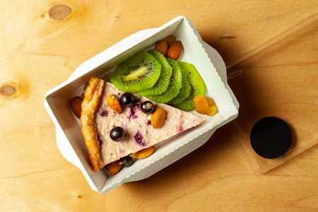 Cheesecake with blueberries, almond, raisins and sliced kiwi in cardboard box on wooden background. Stock Photo