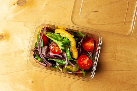 Vegetable salad in a plastic box with plastic fork