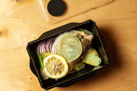 Fish fillet with vegetables and spices in a cardboard box Stock Photo