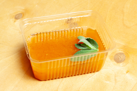 Orange jelly with mint on wooden table