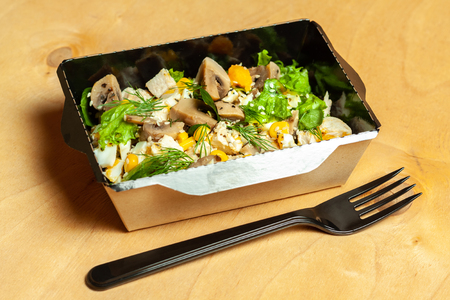 Nourishing salad with chicken and vegetables in a cardboard box