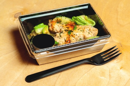 Grilled chicken with avocado, parsley and young onions in a cardboard box Stock Photo