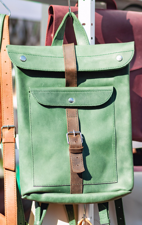 Green leather backpack in the bright midday sun