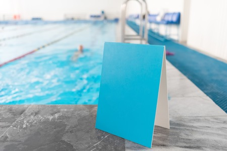 Empty blue sign near the swimming pool background. Stock Photo