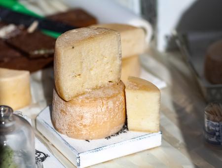 Farm organic cheese. Cheese heads on a cutting board. Cheese Fair