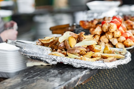 Baked potatoes in foil. Street food background Stock Photo