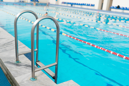 Swimming pool handrails. Clear blue water on background.