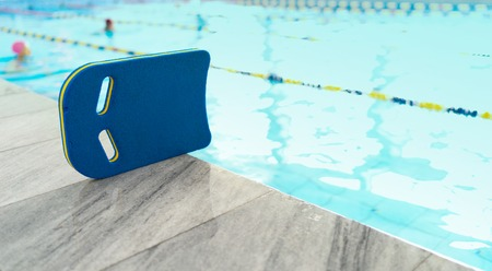 Swimming kickboard on the marble. Swimming pool on background.