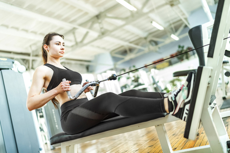Young women doing exercise in seated cable row pull machine