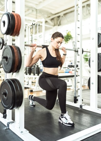 Girl squatting on one knee with a barbell in power rack Stock Photo
