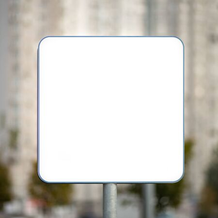 Blank white road sign on blurry urban background