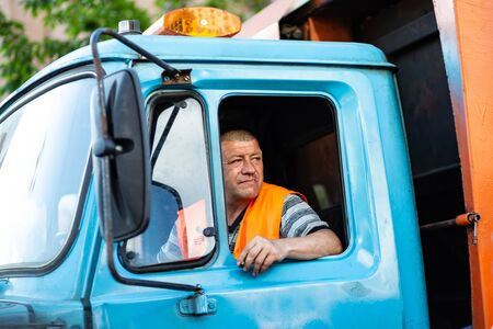 Kyiv, Ukraine, may 26, 2019. Garbage truck driver smokes in the truck cab