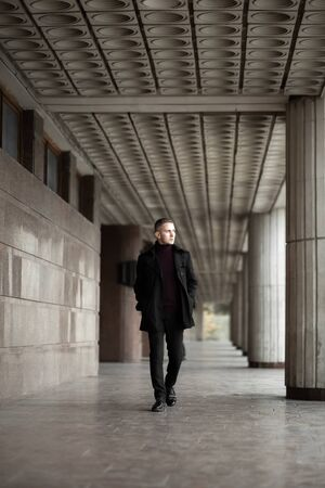 Stylish man in black trench coat and polo neck walks by the modernist building