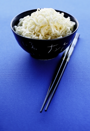 A bowl of noodles and chopsticks photo