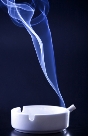 Blue cigarette smoke in black background photo