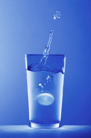Soluble pill dropping into a glass of water photo