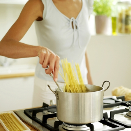 Woman stirring spaghetti in pot photo