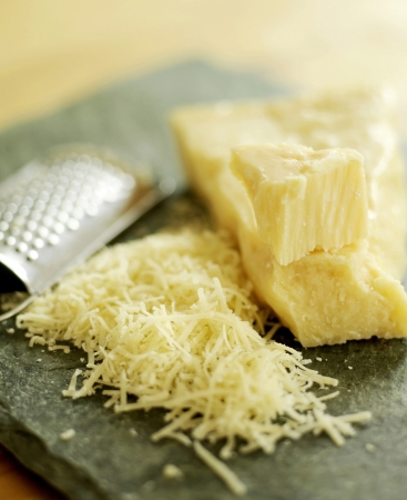 Grated parmesan cheese on a wooden board with grater