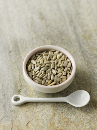Sunflower seeds in pink bowl with white spoon photo