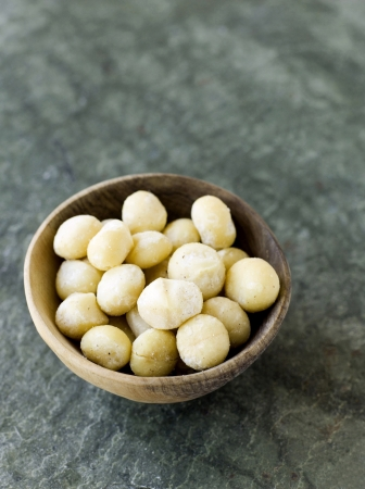 Macadamia nuts in bowl Stock Photo