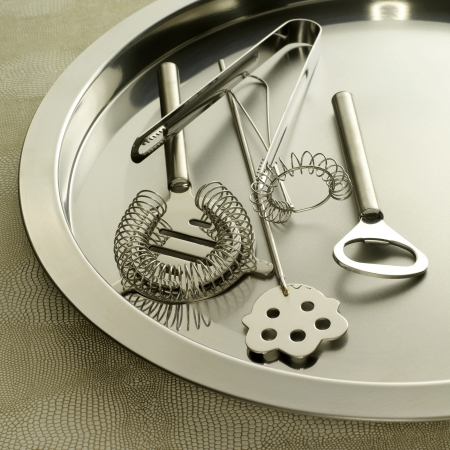 barware: Cocktail making tools (whisk, strainer, tray, bottle opener, ice tongs, and stirrer) Stock Photo