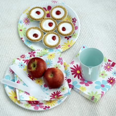 picnic blanket: Bakewell tartas, manzanas rojas, taza y cubiertos de pl�stico sobre una manta de picnic Foto de archivo