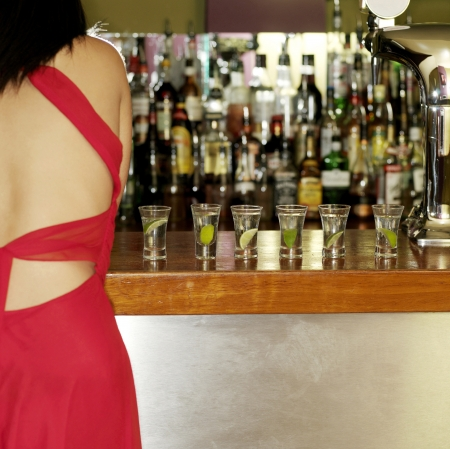 A lady standing in front of a bar counter photo