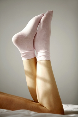 Woman wearing socks relaxing on bed photo