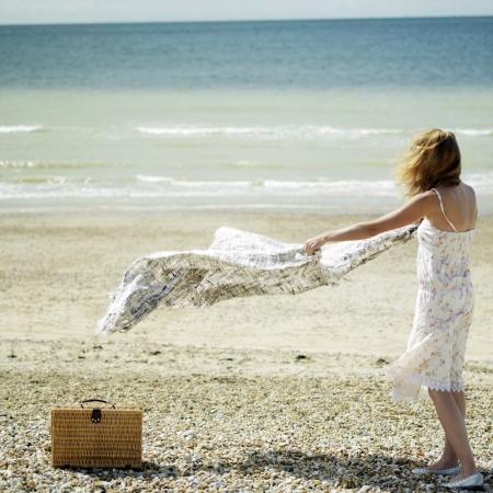 picnic blanket: Mujer que se establecen manta para picnic en la playa Foto de archivo