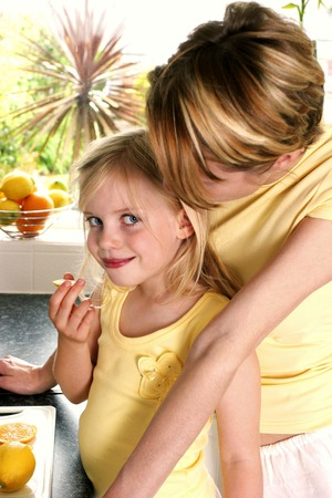A woman watching her daughter eating lemon photo