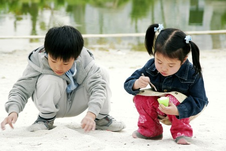 A boy and a girl squatting on the lakeside playing with sand photo