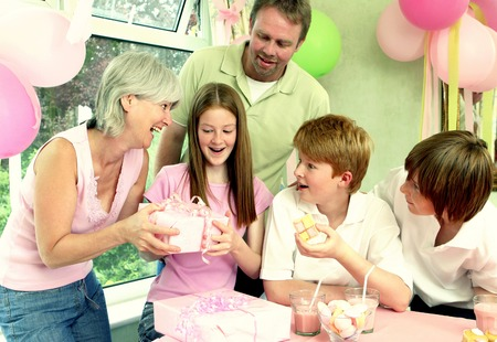 he   my sister: A girl happily receiving her birthday present from her mother while the others watching Stock Photo