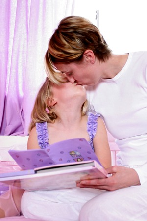 A woman sitting on the bed kissing her daughter photo