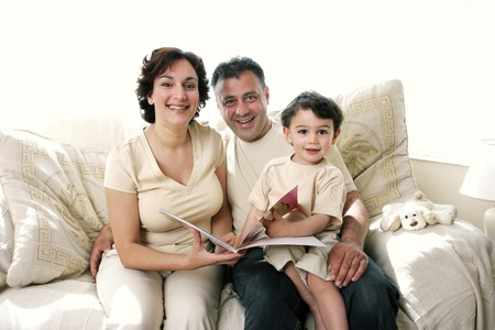 A couple sitting on the couch reading a book for their young son  photo