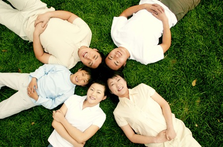 he   my sister: Top angle view of a family lying on the grass in circle