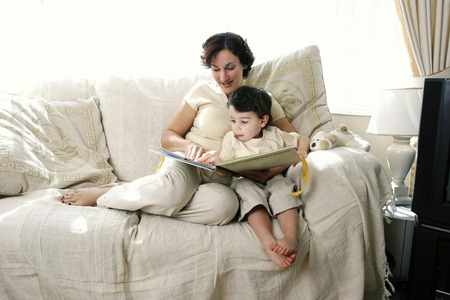 A woman sitting on the couch reading a story book for her young son photo