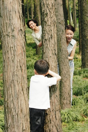 A boy playing hide and seek with his mother and grandmother in the forest photo