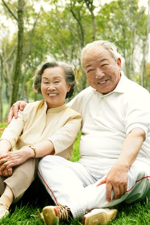 An old couple sitting together on the grass photo