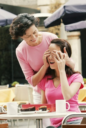 A woman closing her daughters eyes asking her to guess her present