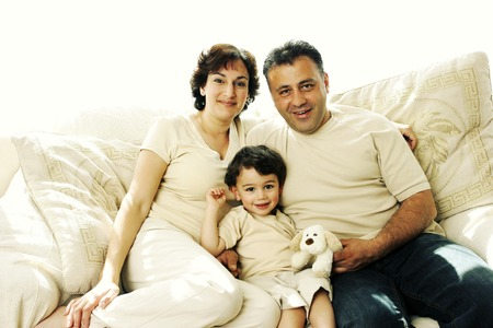 A young boy sitting on the couch with his parents photo
