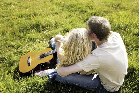Top angle view of a couple sitting on the grass hugging photo