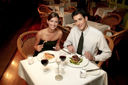 dinner wear: A couple in dinners wear celebrating their anniversary by eating in the restaurant