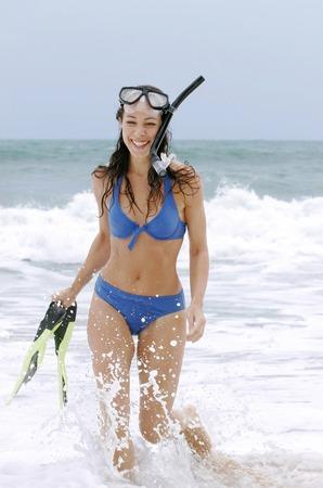 bikini bleu: Une dame heureuse en bikini bleu revenant de la plong�e avec tuba