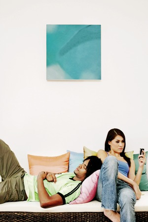 An African American man laying on the couch sleeping while his girlfriend is text messaging Stock Photo