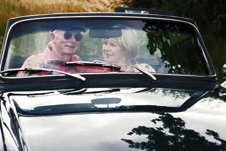 A married couple sitting together in their roofless car photo